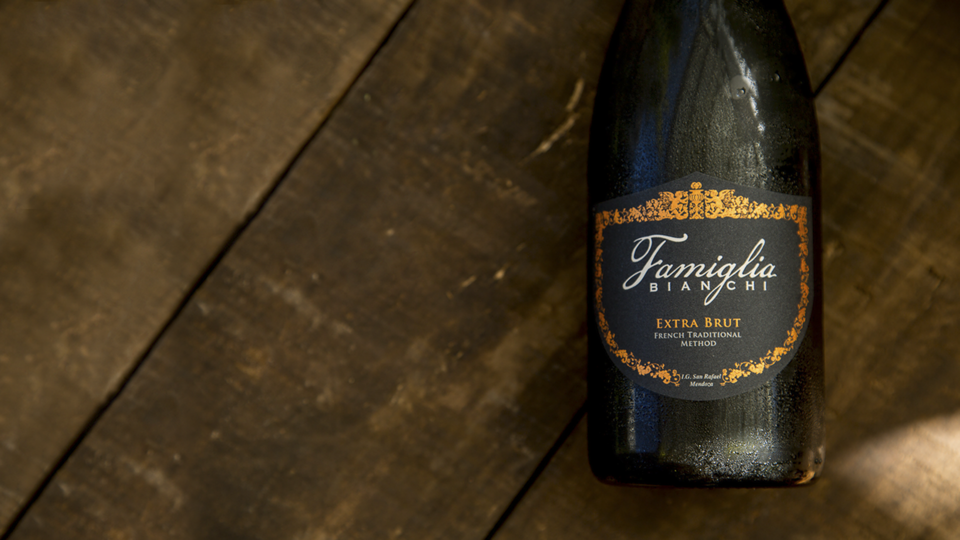 Famiglia Extra Brut bottle over wooden background